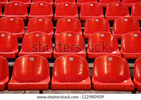 Wet bright red stadium seats after rain - stock photo