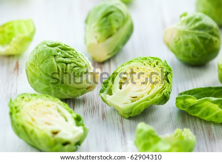 Wet brussels sprouts  on the white wooden table - stock photo