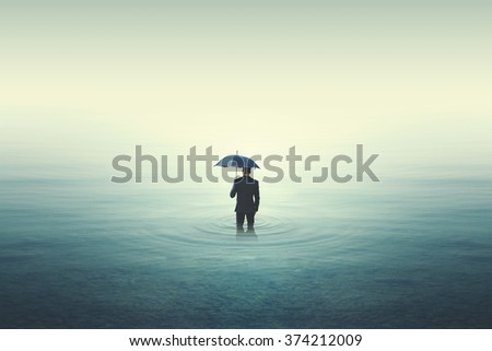 Wet business man walking into water - stock photo