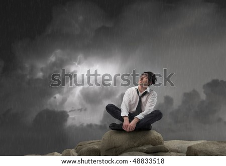 Wet businessman sitting on a rock with cloudy sky on the background - stock photo
