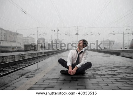 Wet businessman sitting on the platform of a train station - stock photo