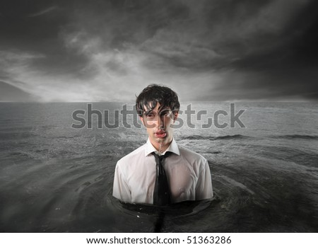 Wet businessman standing in the water - stock photo