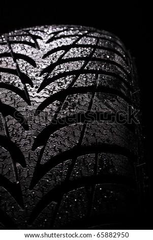 wet car tire on black background - stock photo