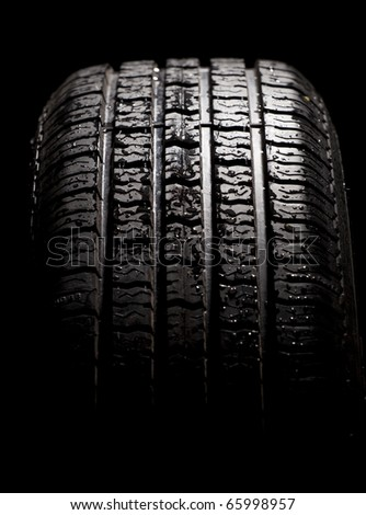 Wet car tyre on black studio background