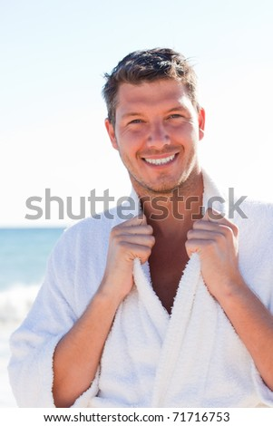 Wet Carefree male walking down the coastline with bathrobe - stock photo