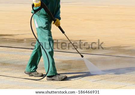 Wet cleaning of city streets with high-pressure cleaner - stock photo