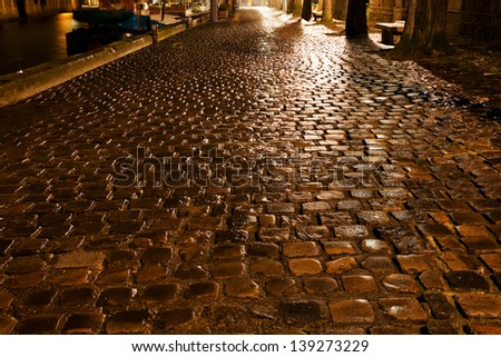 wet cobblestone pavement quay in Paris at night - stock photo