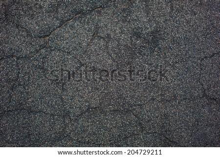 wet cracked tarmac road surface - stock photo
