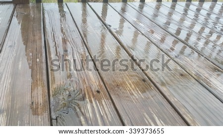 Wet deck in the rain with reflection of rail - stock photo