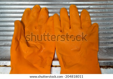 Wet dirty orange rubber gloves are on sink.