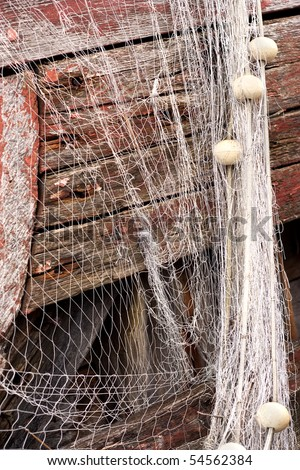 Wet fishing net with corks is hanging on the old rusty fishing boat. - stock photo