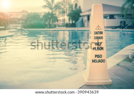 Wet floor warning sign on a swimming pool - stock photo