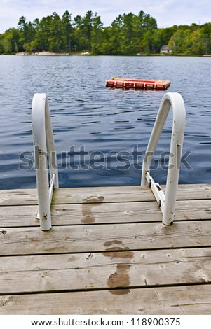 Wet footprints on dock with ladder and diving platform at lake in Ontario Canada - stock photo