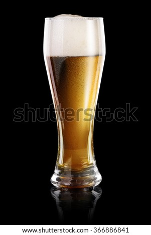 Wet Glass of fresh beer isolated on black background - stock photo
