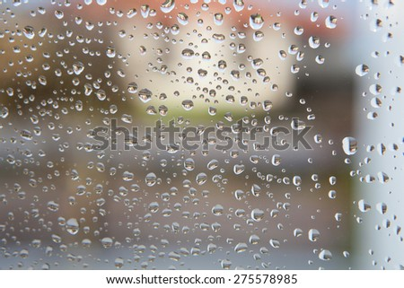 Wet glass with drops of rain fall on the street,
