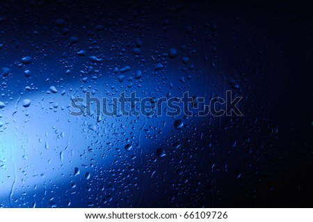 Wet glass with water droplets in blue light abstract artistic background texture - stock photo