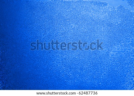 Wet glass with water drops in blue tone - stock photo