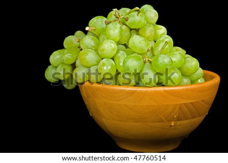 wet green grapes in wooden bowl