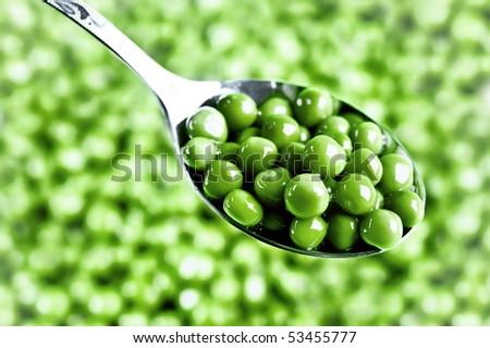 wet green peas on the spoon - stock photo
