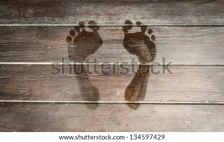 Wet human footprints on dark wooden plank floor. Walk from beach to hotel or home. Abstract backgrounds and wallpapers. Holidays and vacations in summer. - stock photo