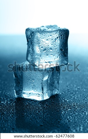 wet ice cubes on black glossy background - stock photo