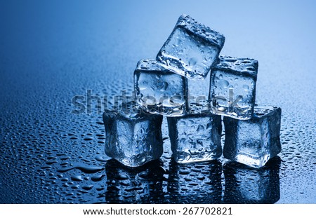 wet ice cubes on blue background with water drops  - stock photo