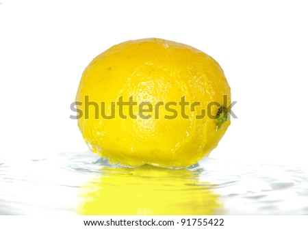 Wet juicy lemon in water, isolated on white - stock photo