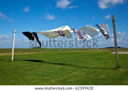 wet laundry drying on clothes line against a blue sky