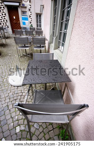 Wet metallic tables and chairs in rainy day at pavement cafe  - stock photo