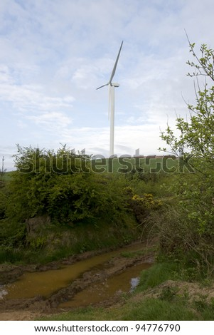 wet mucky dirt road to a windmill on lush irish countryside landscape in glenough county tipperary ireland - stock photo