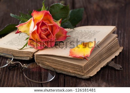 wet orange rose on old brown wooden table with old bible book and vintage glasses - stock photo