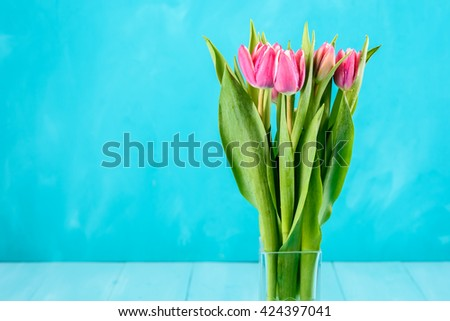 Wet Pink Tulip Flowers In Vase On Turquoise Table - stock photo