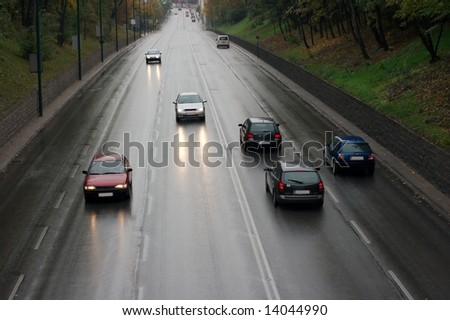 wet road with traffic passing by - stock photo