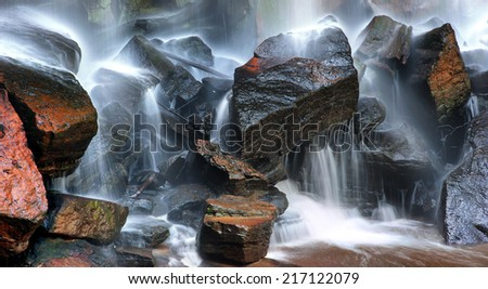 Wet rocks and water streams of mountain river - stock photo
