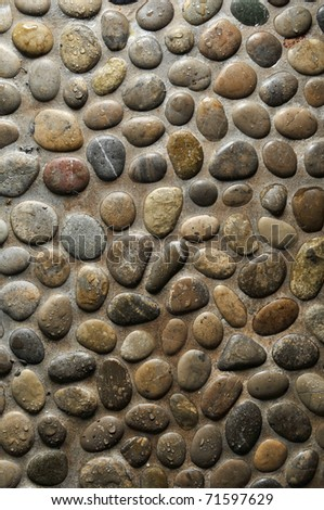 Wet round stone rock texture with tiny water drops on them and dramatic lighting. - stock photo