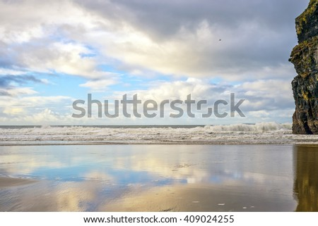 wet sand and cliff reflections on the wild atlantic way in Ballybunion Ireland - stock photo