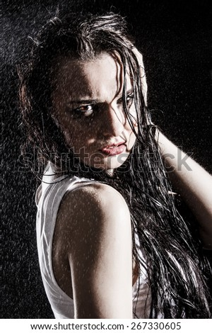Wet sexy woman covered with water drops over black background - stock photo