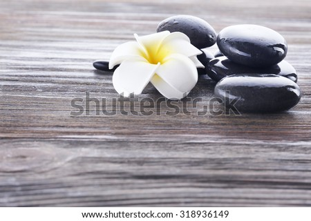 Wet spa stones with flower on wooden background - stock photo