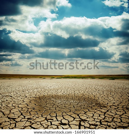 wet spot on cracked earth under dramatic sky - stock photo