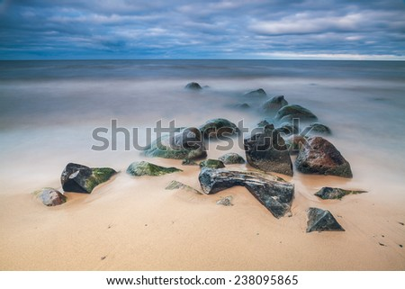 Wet stones on the sandy lake shore. Long exposure