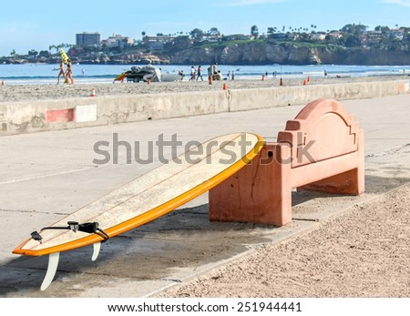 Wet surfboard with water drops on surface resting on a stone bench at a suburban beach. Paved pedestrian walkway. People on the sand and in ocean. Hills, cliff, buildings in blurred background. - stock photo