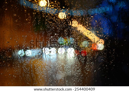 Wet the car window with the background of the night city lights - stock photo