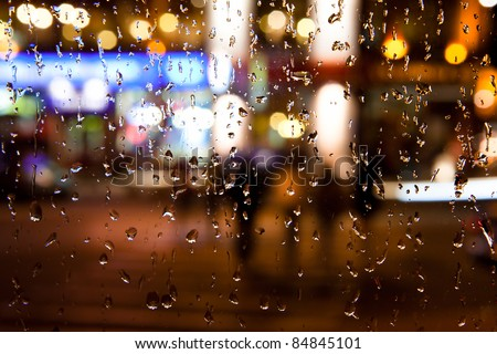 Wet the window with the background of the autumn night city - stock photo