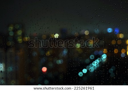 Wet the window with the background of the night city traffic view. - stock photo