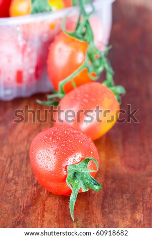 wet tomatoes closeup on wooden table - stock photo