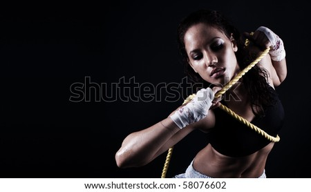 wet Toned female fitness body holding a rope - stock photo