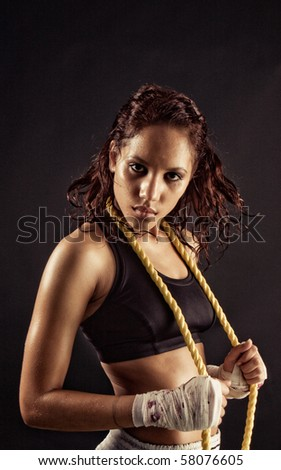 wet Toned female fitness body holding a rope after workout - stock photo