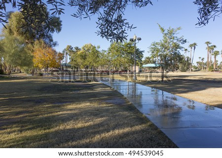 Wet walkway among shady green trees in Phoenix downtown Encanto park, Arizona