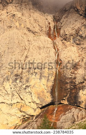 Wet walls of Sella massif with small waterfall under the clouds, Dolomite Alps, Italy - stock photo