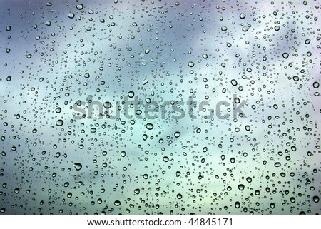 Wet window with rain drops and a cloudy stormy sky outside - stock photo